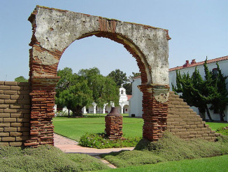 Adobe arch in mission courtyard. Photo by Geographer.